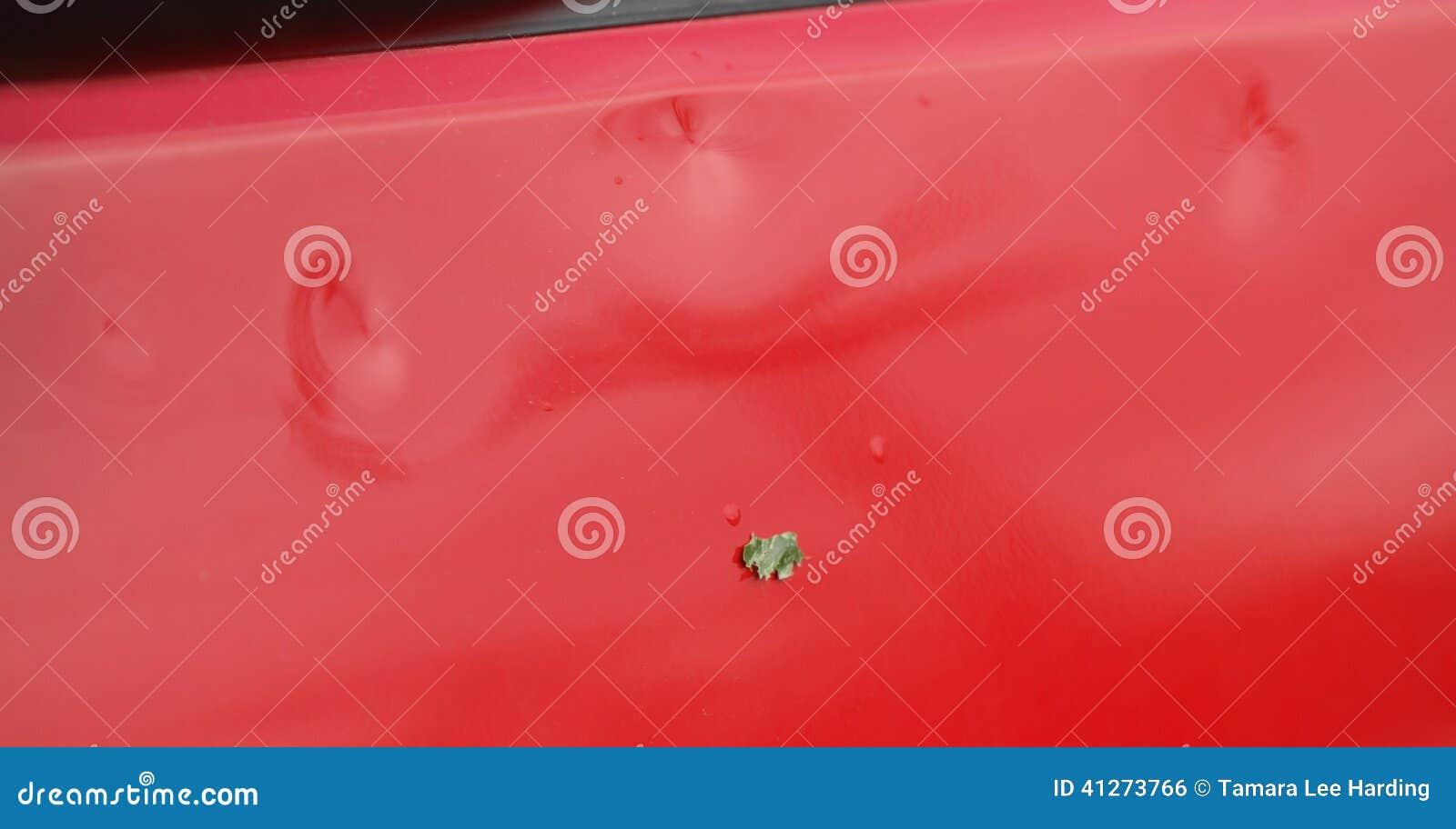 Szczegół grad szkoda na czerwonym pojazdzie