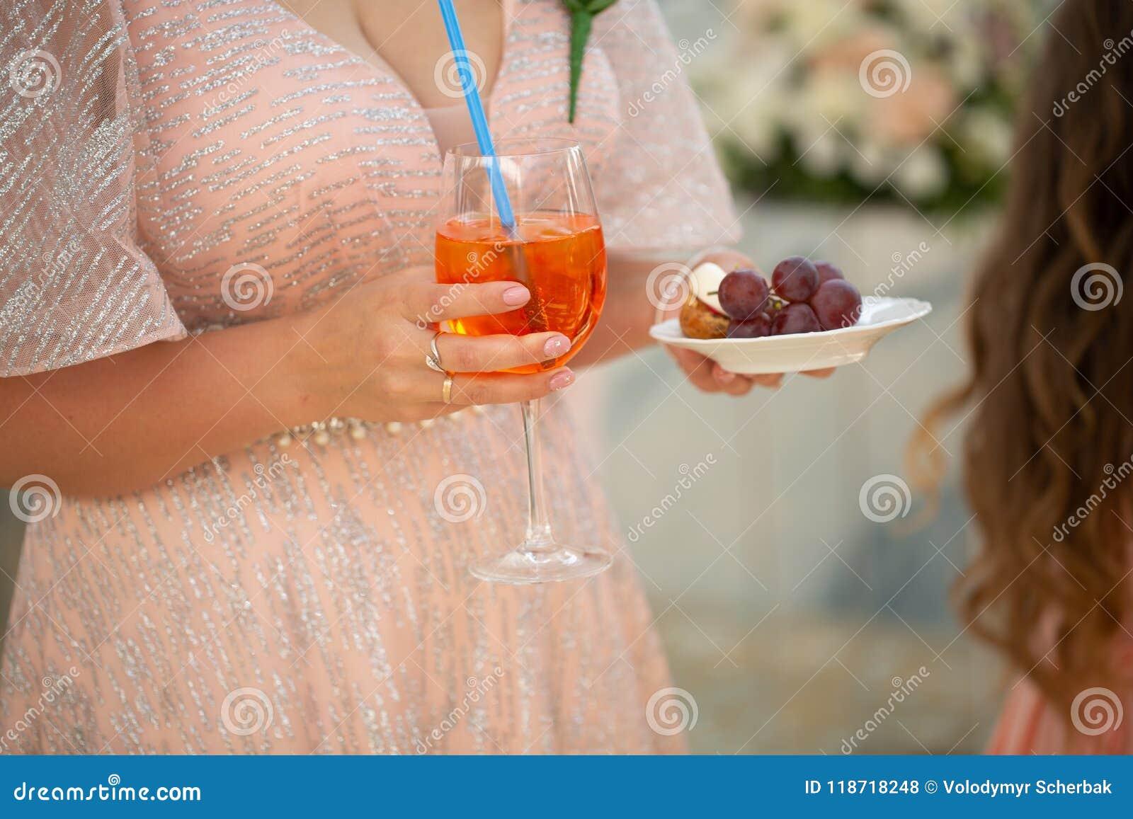 Szczegół kobiety ręka z koktajlu szkła czerwieni napojem