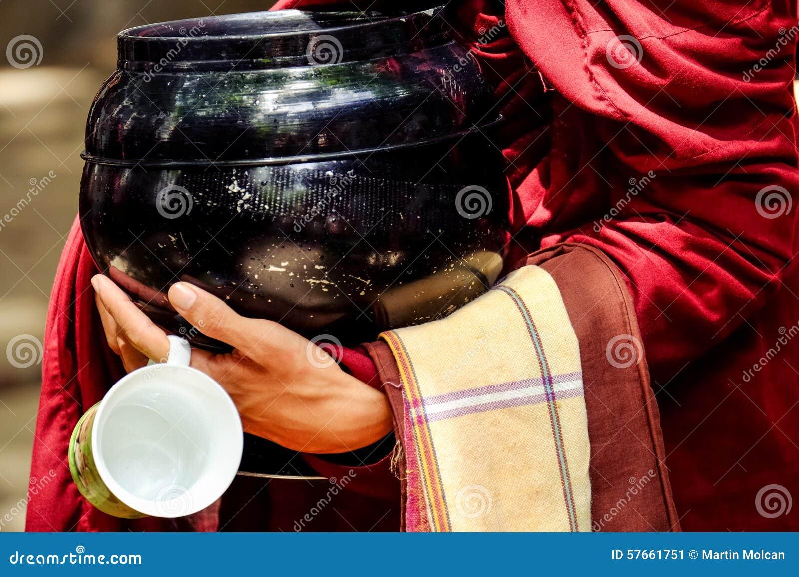Szczegół mnich buddyjski wręcza trzymać filiżankę i puchar