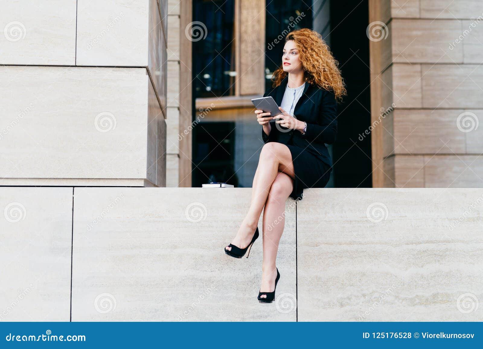 Szczupły bizneswoman z falistym luksusowym włosy, mieć nikłe nogi, będący ubranym czarnego kostium, eleganckich buty trzyma pasty