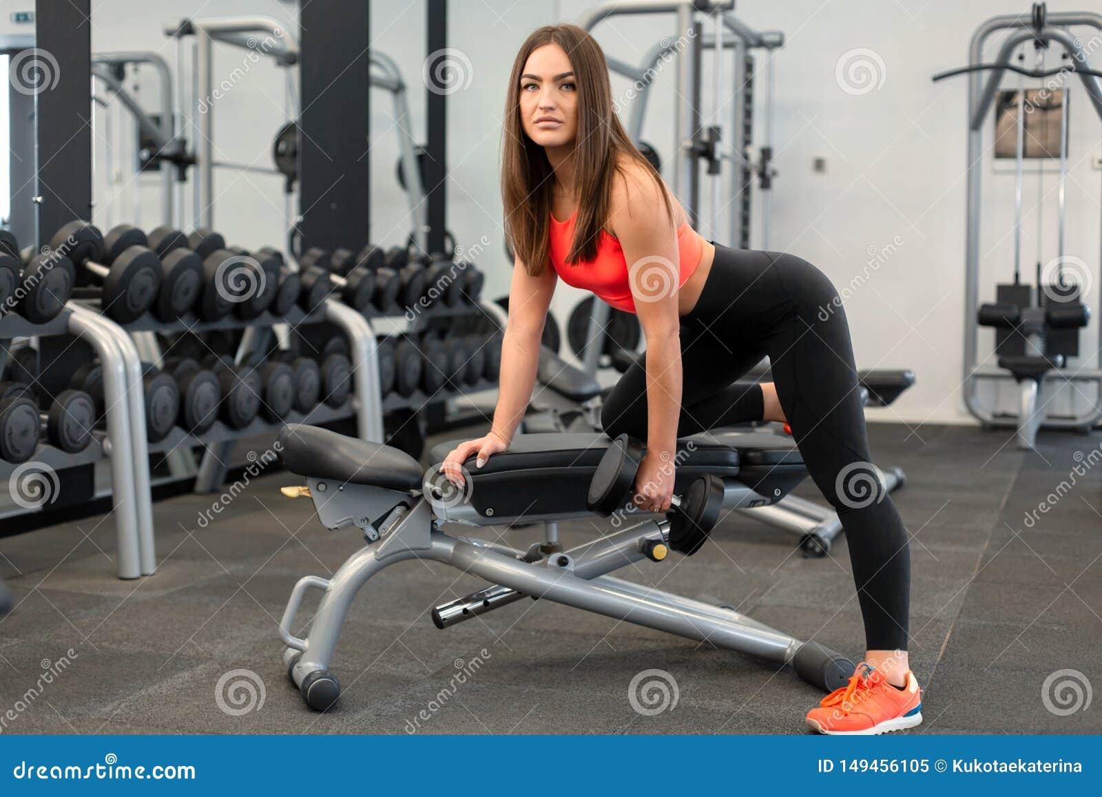 Szczupli kobiet exercis z dumbbells na ?awce przy gym