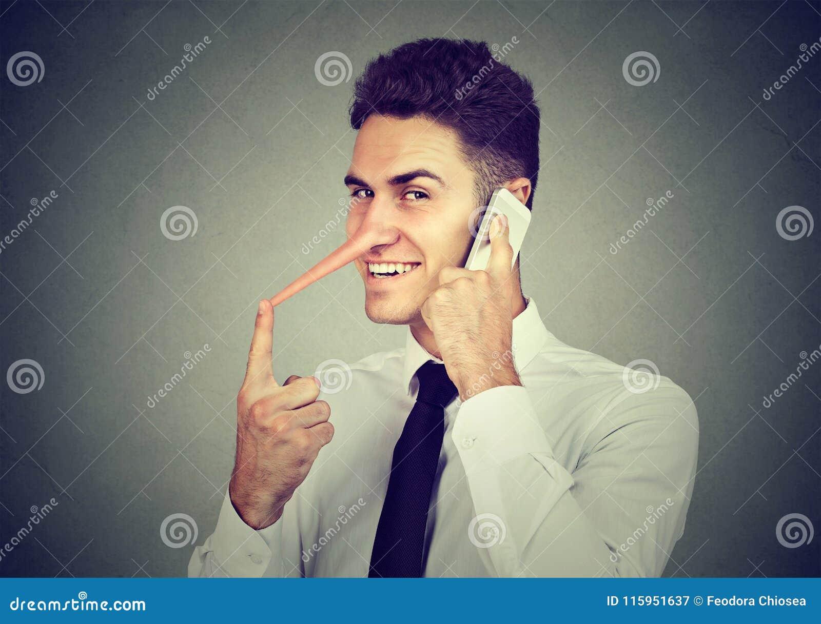 Szczwany młody człowiek opowiada na telefonie komórkowym na szarość z długim nosem izoluje tło Kłamcy pojęcie
