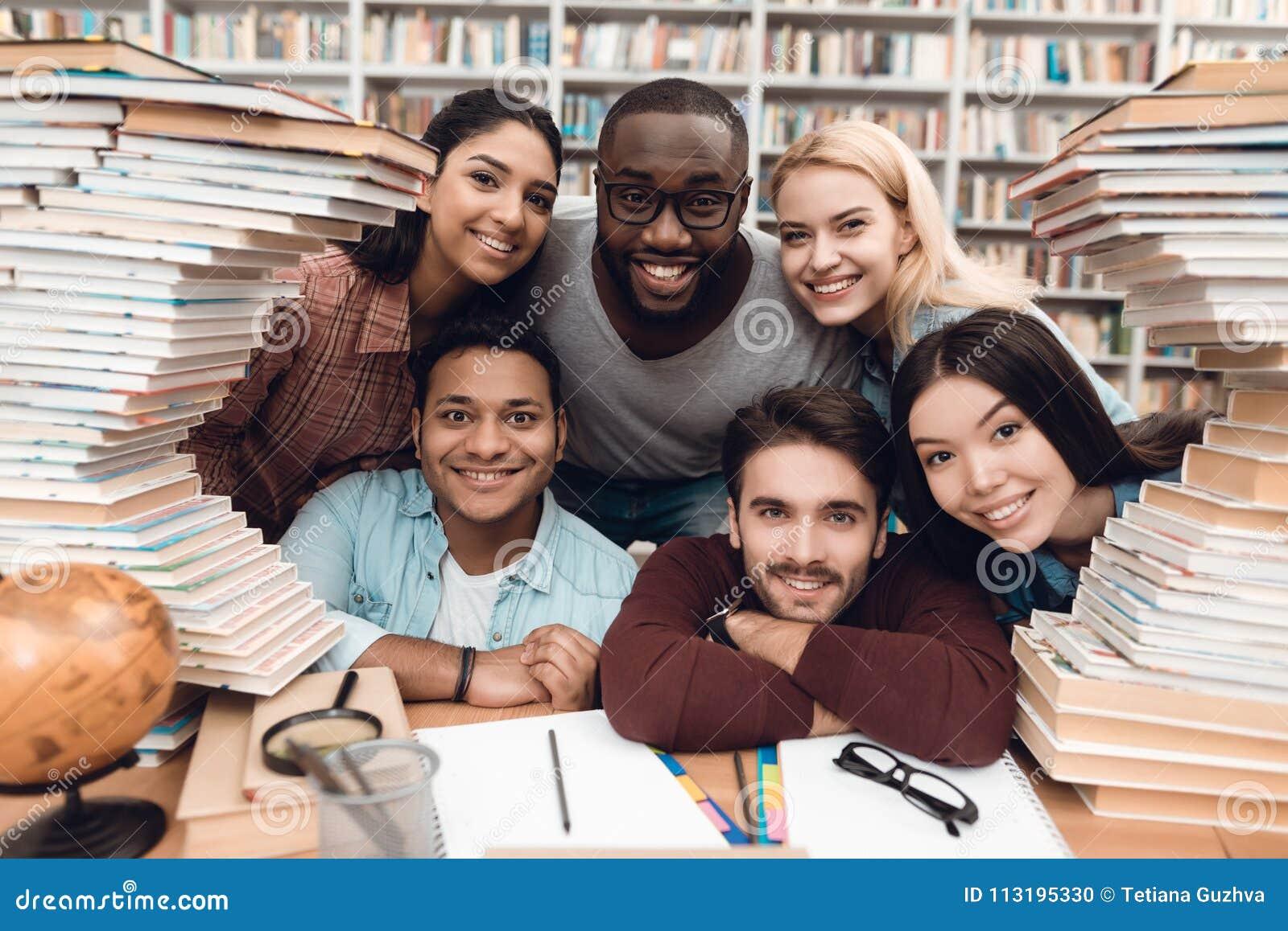 Sześć etnicznych uczni, mieszającej rasa, hindus, azjata, amerykanin afrykańskiego pochodzenia i biel otaczający z książkami przy
