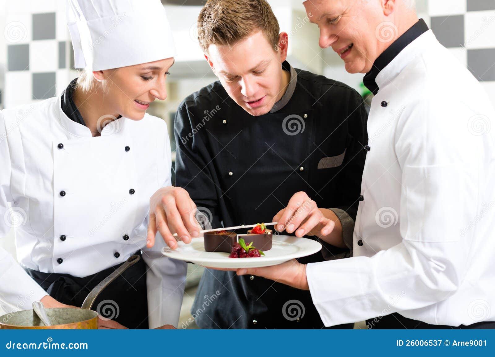 Szef kuchni drużyna w restauracyjnej kuchni z deserem