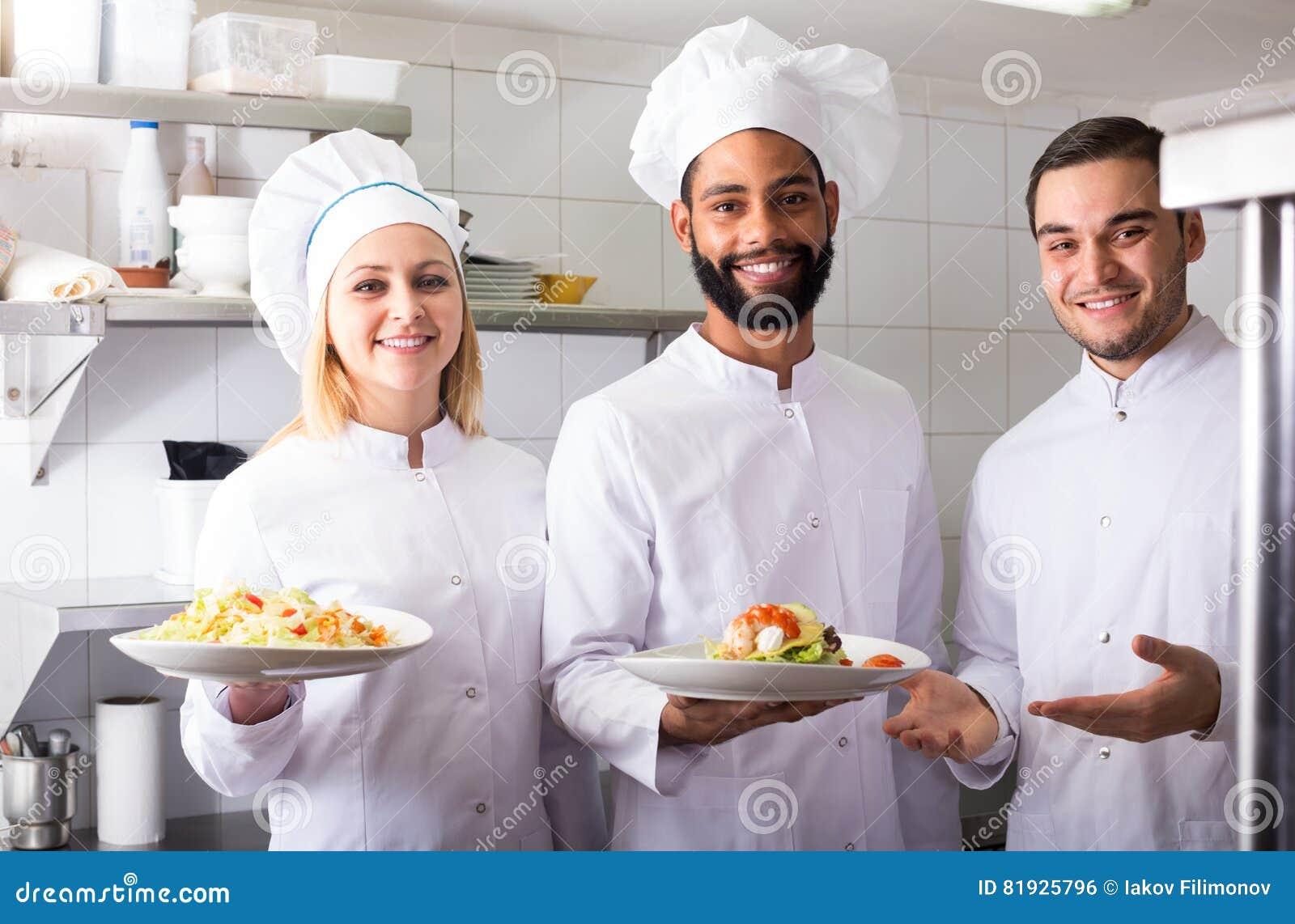 Szef kuchni i jego asystenci przygotowywa posiłek