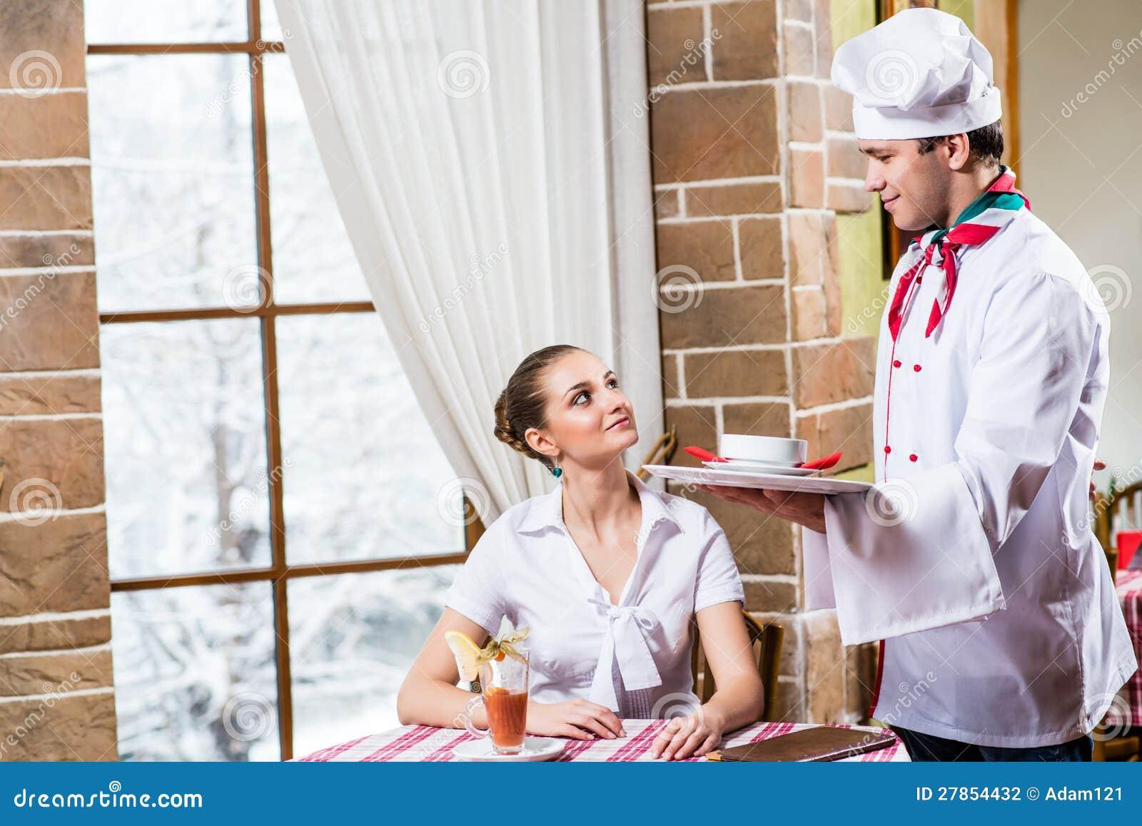Szef kuchni przynosi naczyniu ładnej kobiety w restauraci