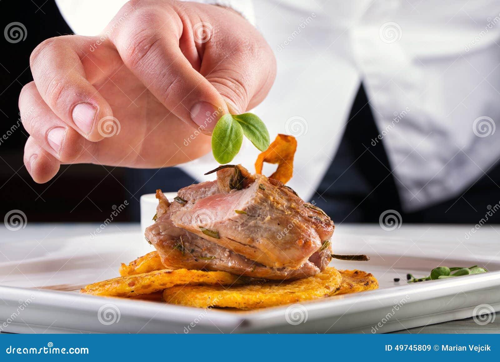 Szef kuchni w hotelowym lub restauracyjnym kuchennym kucharstwie ręka, tylko Przygotowany mięsny stek z kartoflanymi lub selerowy