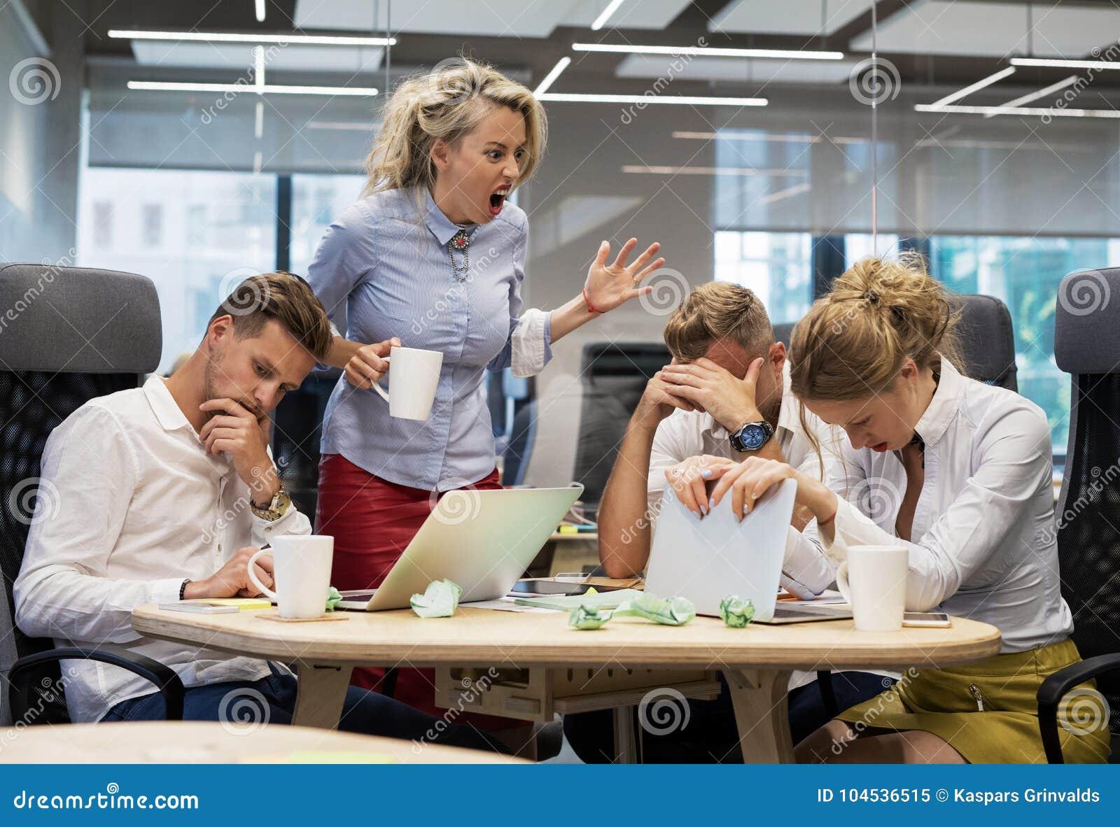 Szef wrzeszczy przy pracownikami w pokoju konferencyjnym