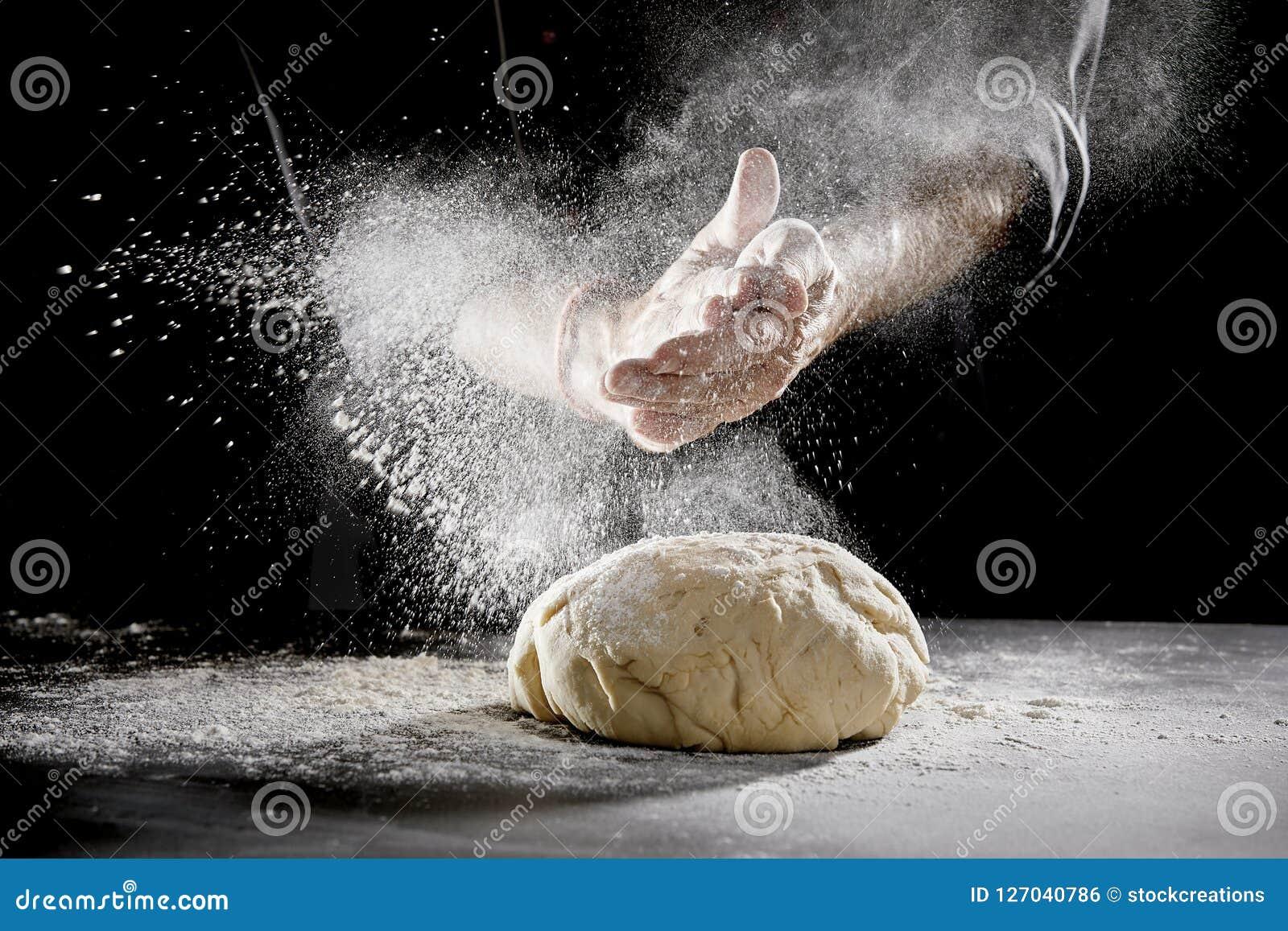 Szefa kuchni rozrzucania mąka podczas gdy ugniatający ciasto