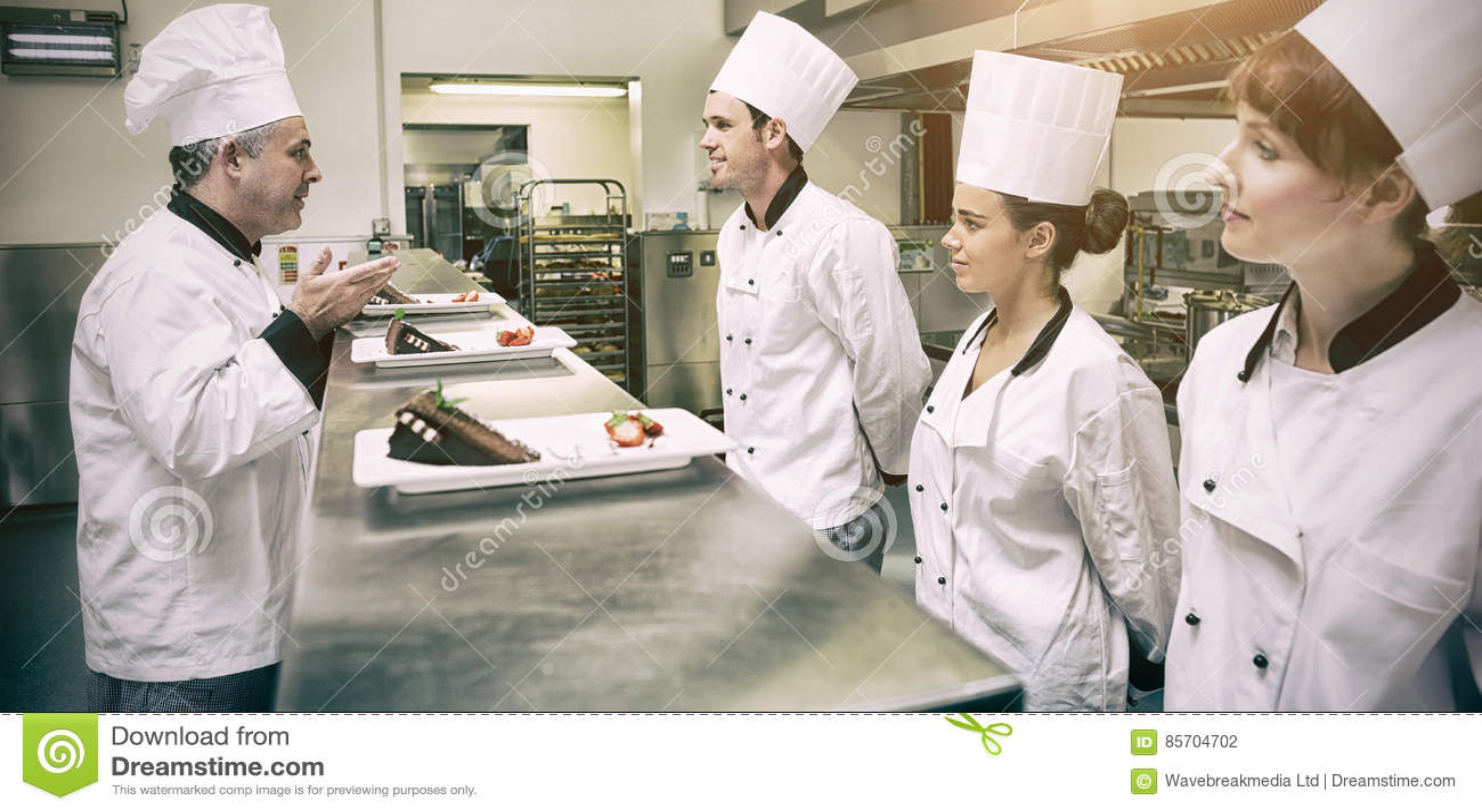Szefowie kuchni przedstawia ich deserowych talerze kierowniczy szef kuchni w kuchni
