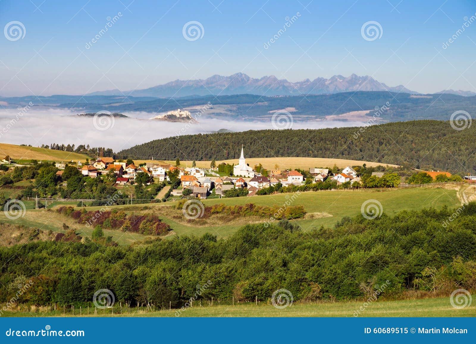 Szenische Ansicht des traditionellen Dorfs, des Schlosses, der Wiesen und des Berges