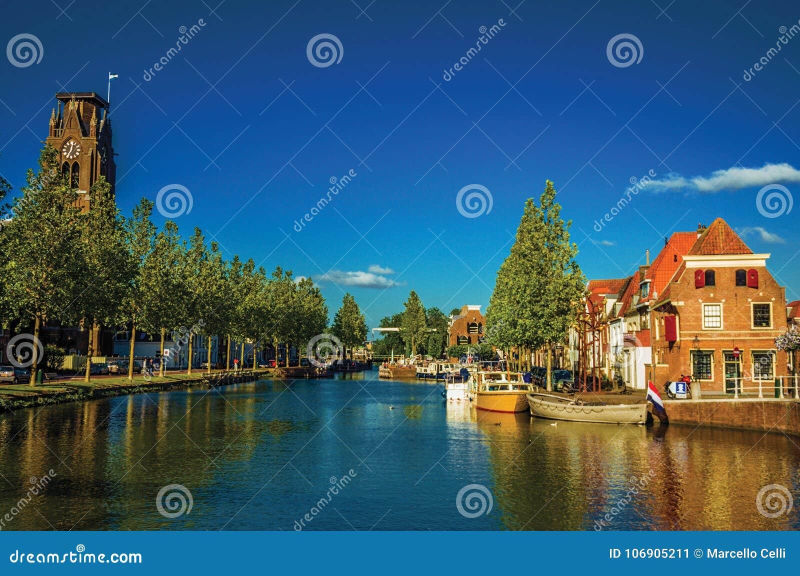Szeroki kanał z cegła domami, łodzie cumować odbijał w wodzie i niebieskim niebie zmierzch w Weesp