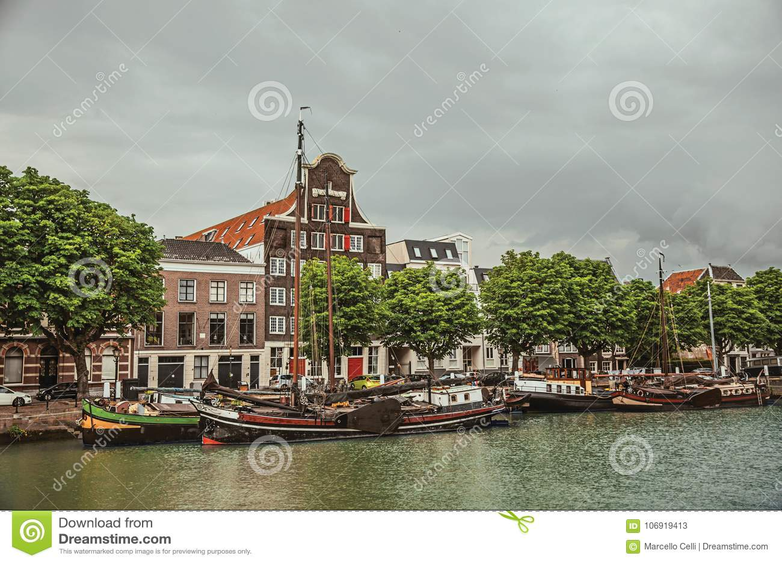 Szeroki kanał z ceglanym domem obok go i udziałów cumować łodzie w chmurnym dniu przy Dordrecht