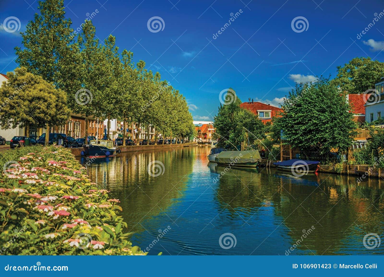 Szeroki kanał z domami i łodziami cumował na swój banku odbijającym w wodzie przy Weesp na zmierzchu