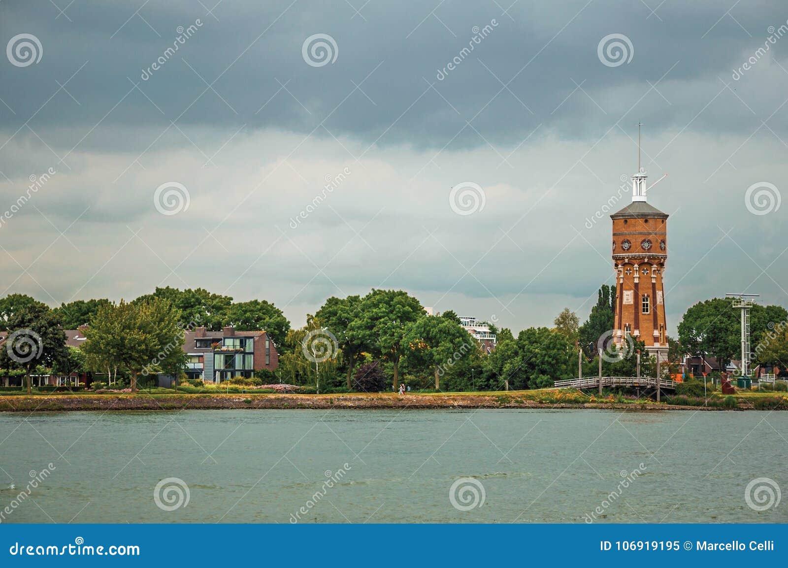 Szeroki kanał z gajem, budynki i cegła, górujemy w horyzoncie na chmurnym dniu przy Dordrecht