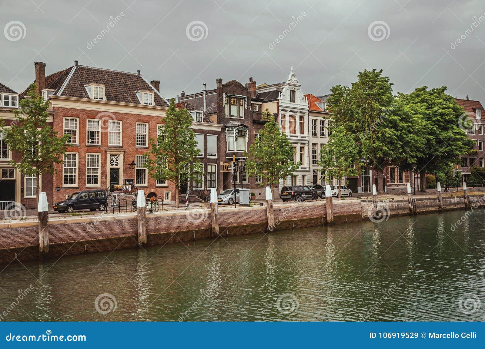 Szeroki wykładający kanał z ceglanymi domami w ulicie obok go i samochodach w chmurnym dniu przy Dordrecht