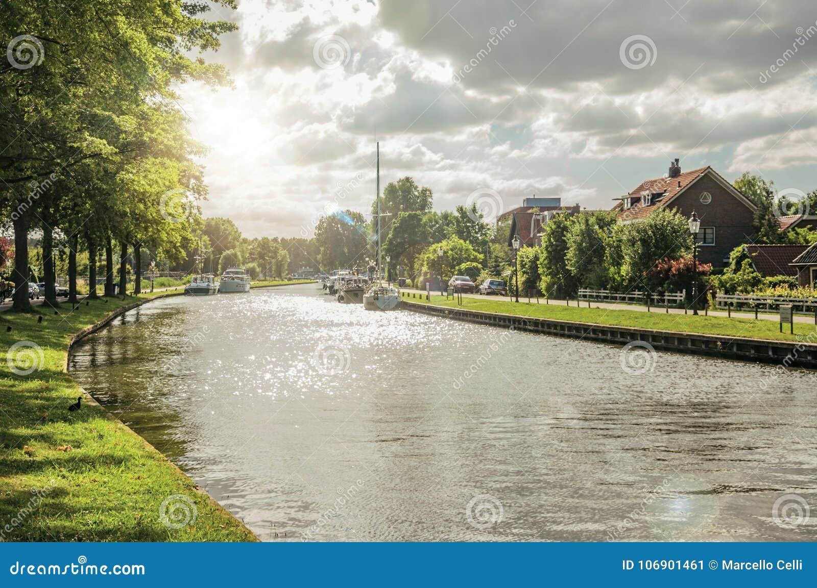 Szeroki wykładający kanał z domami, łodzie i połysk zmierzch odbijał w wodzie przy Weesp