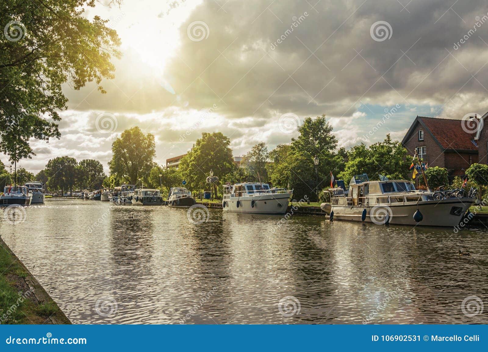 Szeroki wykładający kanał z domami i łódź cumowaliśmy na swój banku na zmierzchu przy Weesp