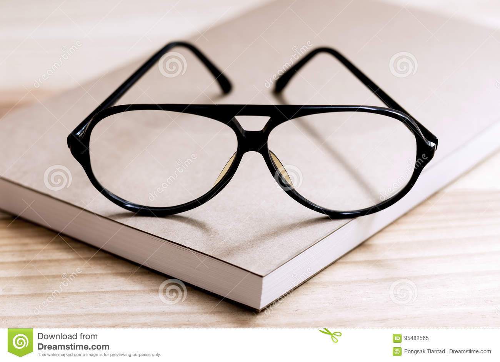 Szkła i książka na drewnianym stole