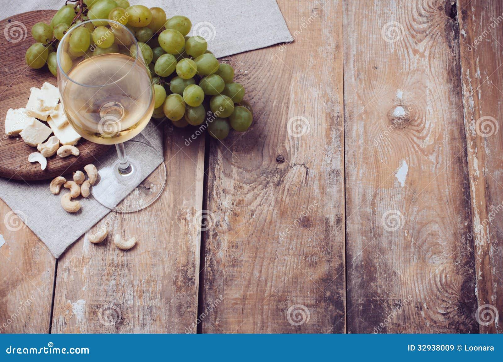 Szkło biały wino, winogrona, nerkodrzew dokrętki i miękki ser,