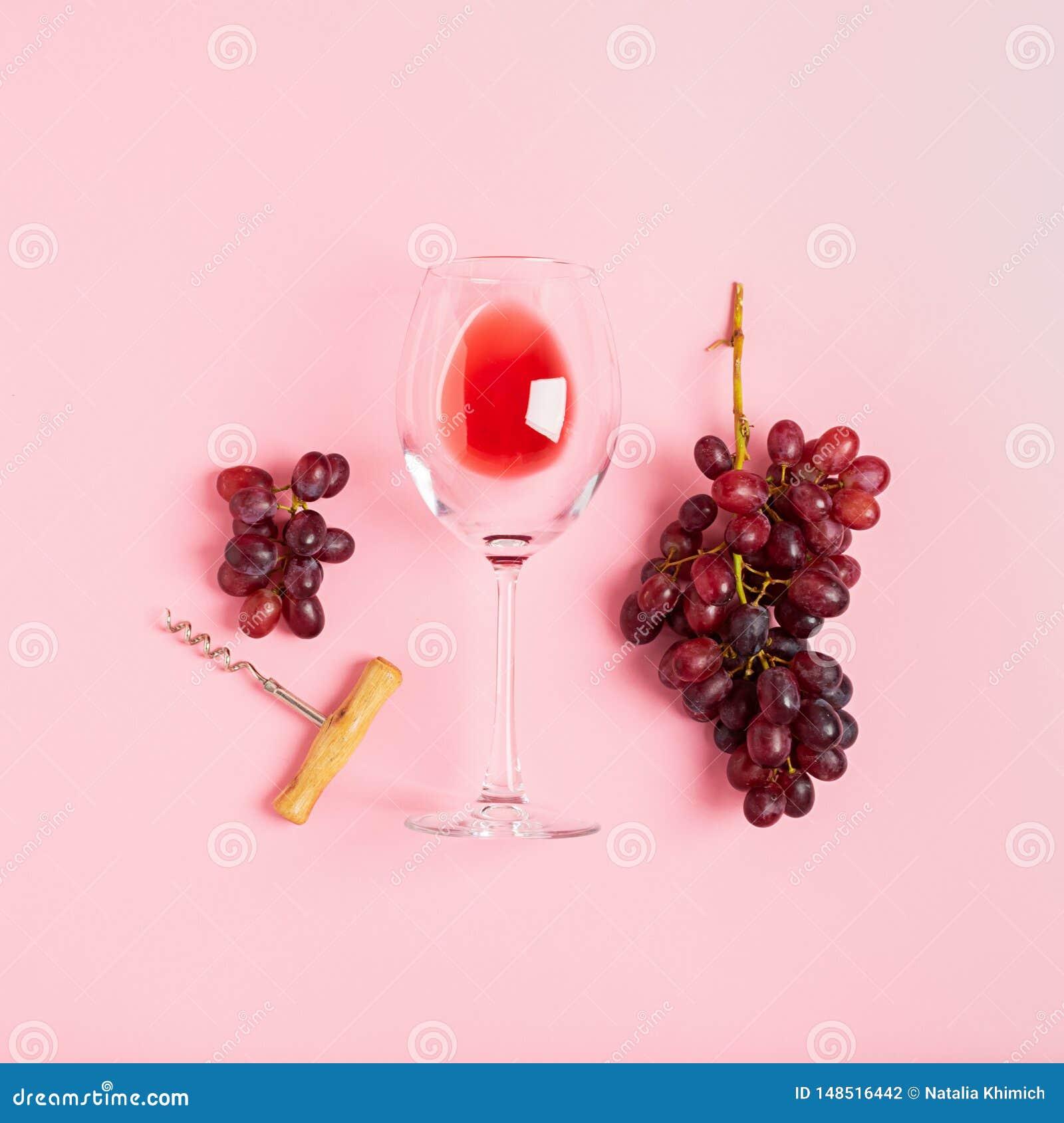 Szkło czerwone wino wiązka winogrona corkscrew na delikatnym różowym tle minimalista Odg?rnego widoku mieszkania uk?ad