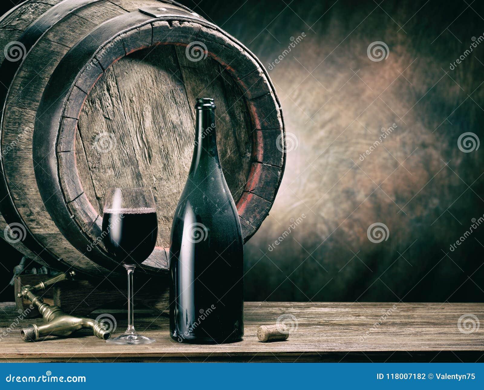 Szkło czerwonego wina i wina butelka Dębowa wino baryłka przy backgroun