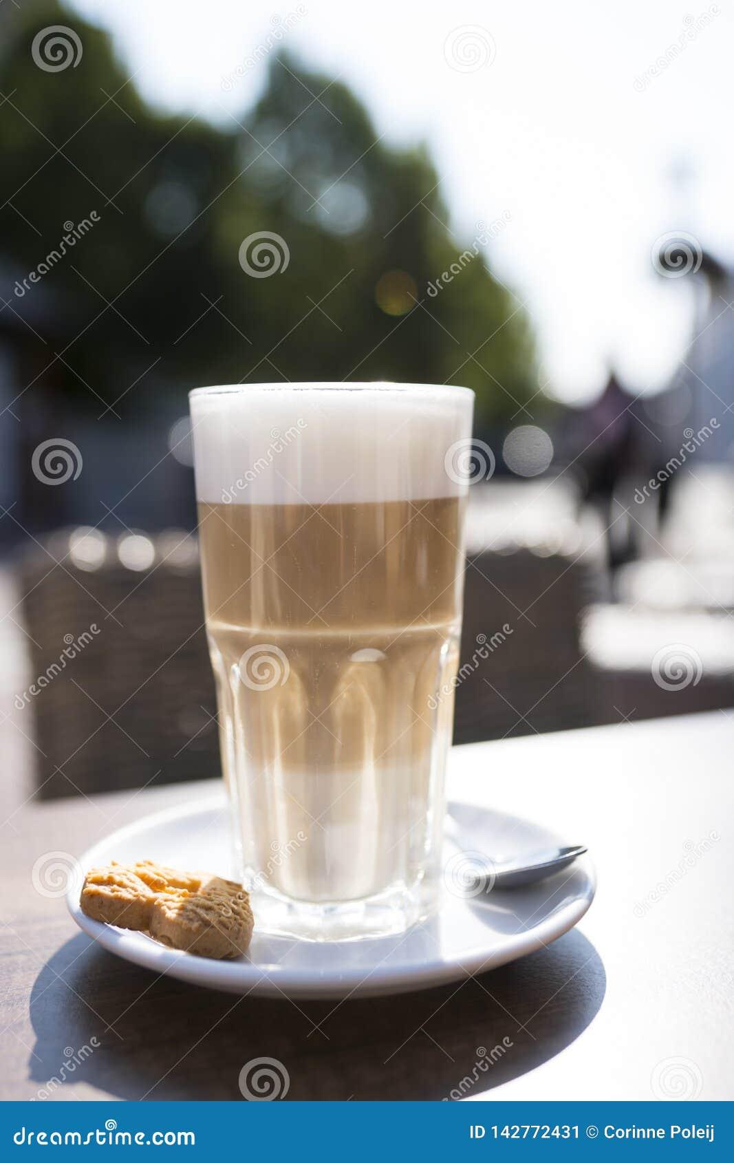 Szkło latte macchiato z spume, łyżką i ciastkiem,
