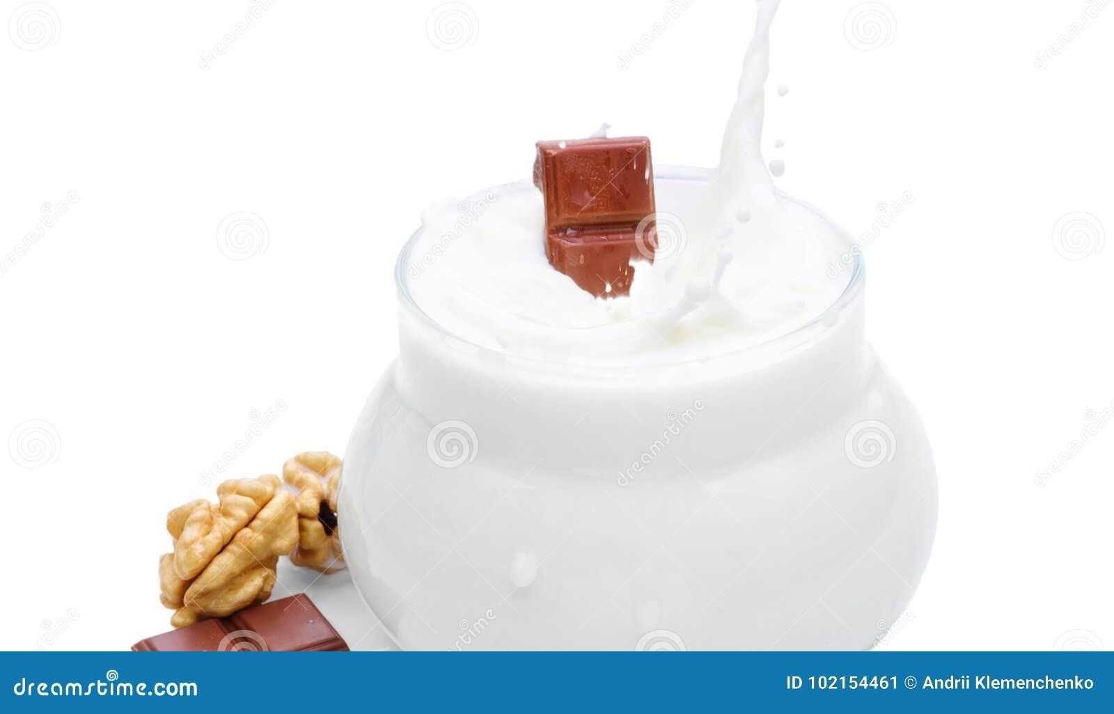 Szkło mleko, dokrętki i kawałek czekolada, Czekolada spada w mleko Odosobniona fotografia na białym tle