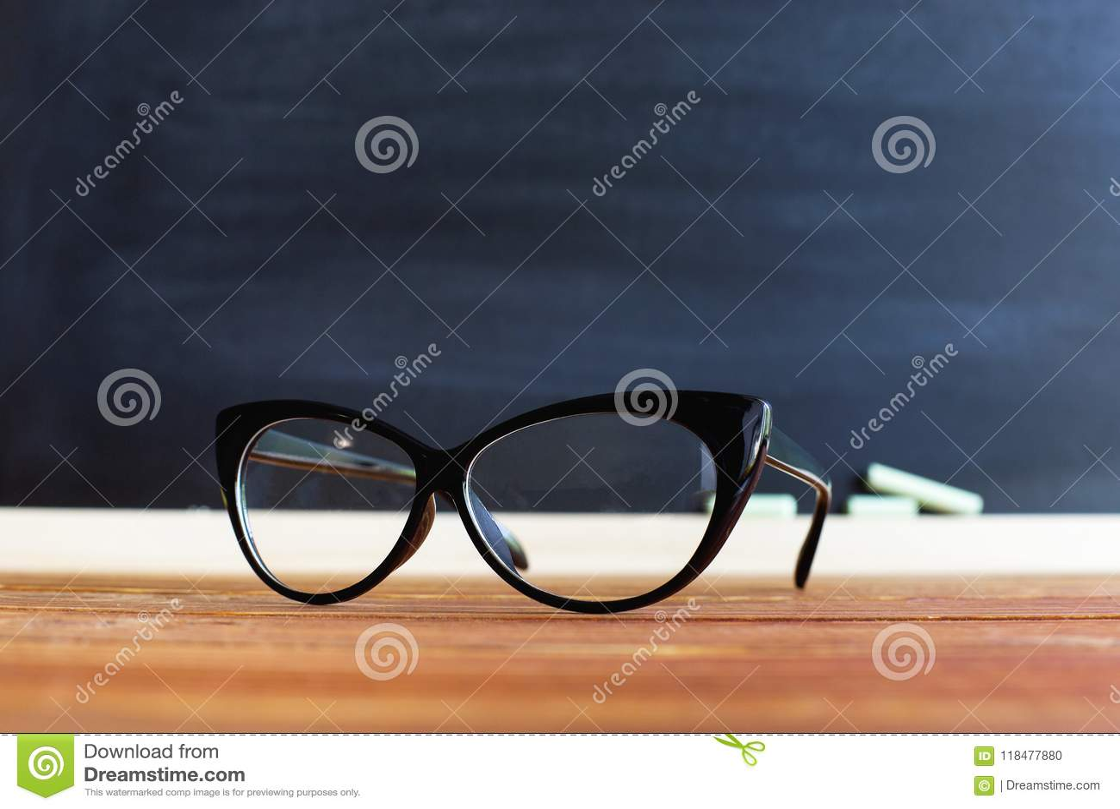 Szkło nauczyciel na stole przeciw chalkboard tłu z kredą, Pojęcie dla nauczyciela dnia kosmos kopii