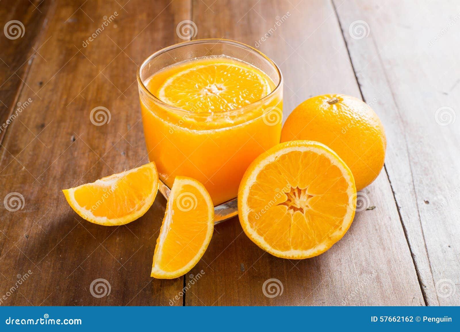 Szkło sok pomarańczowy z plasterkami na drewnianym tle