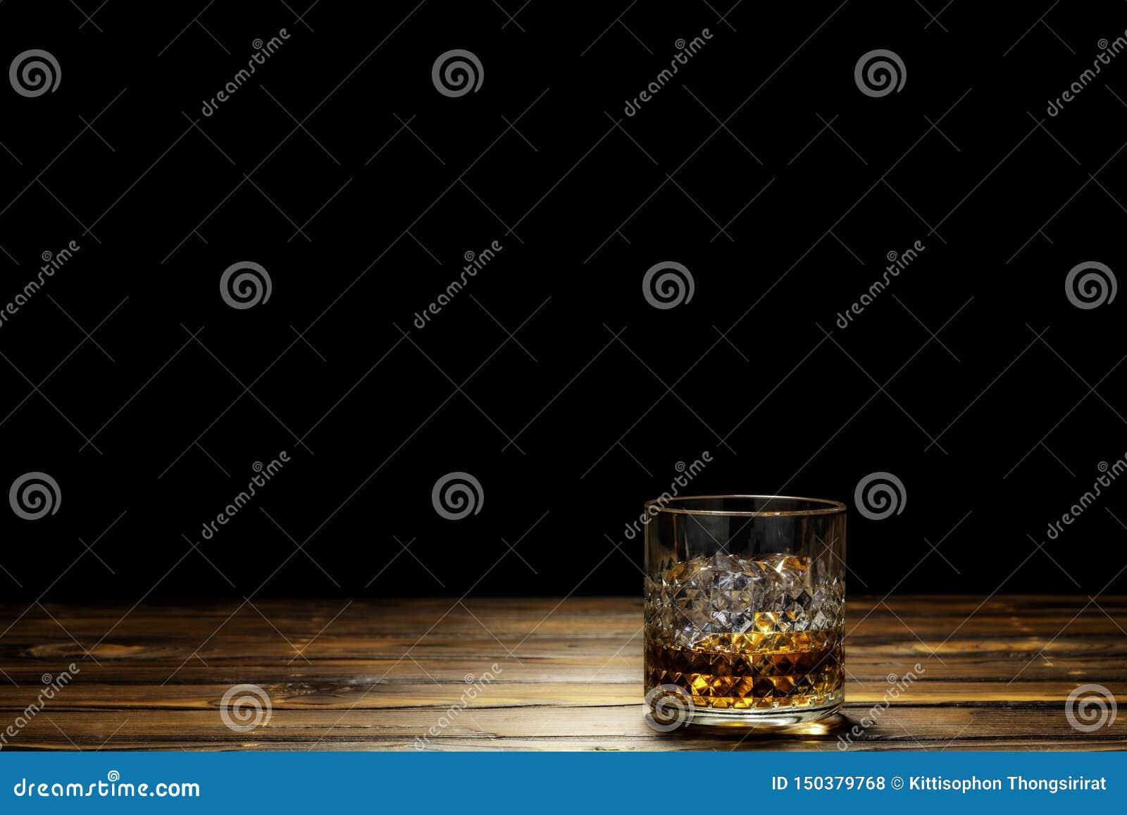 Szkło Szkocki whisky lub whisky na skale z lodem na drewnianym stole w czarnym tle