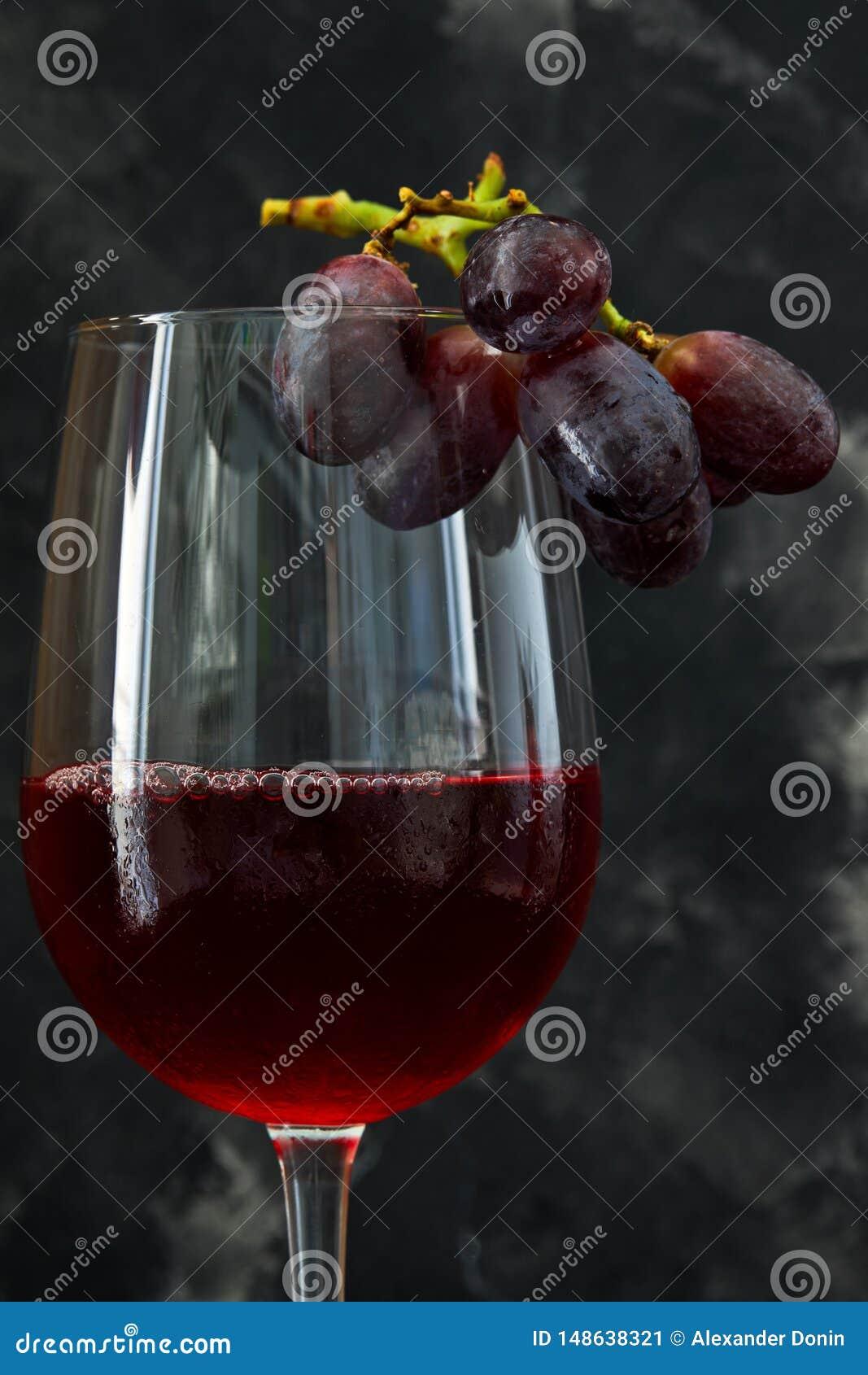 Szkło wino z winogronami na ciemnym tle