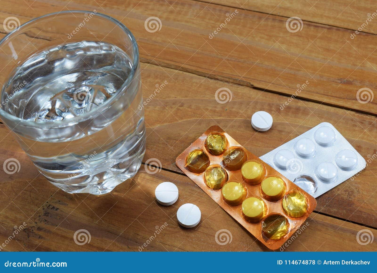 Szkło woda i pastylki na stole, doktorski ` s rozładowanie