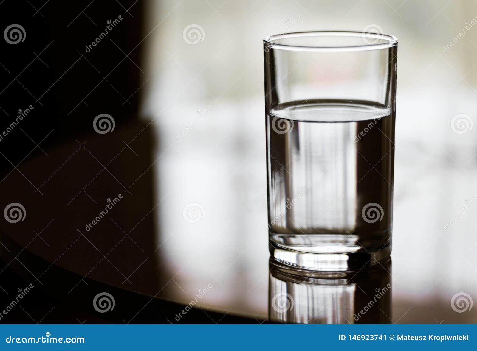 Szkło wypełniający z wodą na odbijającej powierzchni