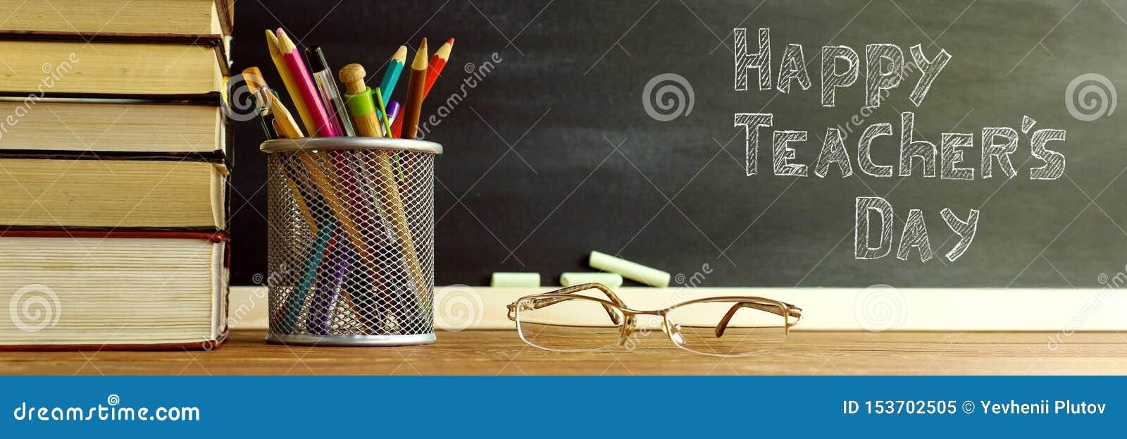 Szk?o nauczyciel rezerwuje i stojak z o??wkami na stole na tle blackboard z kred?, Poj?cie