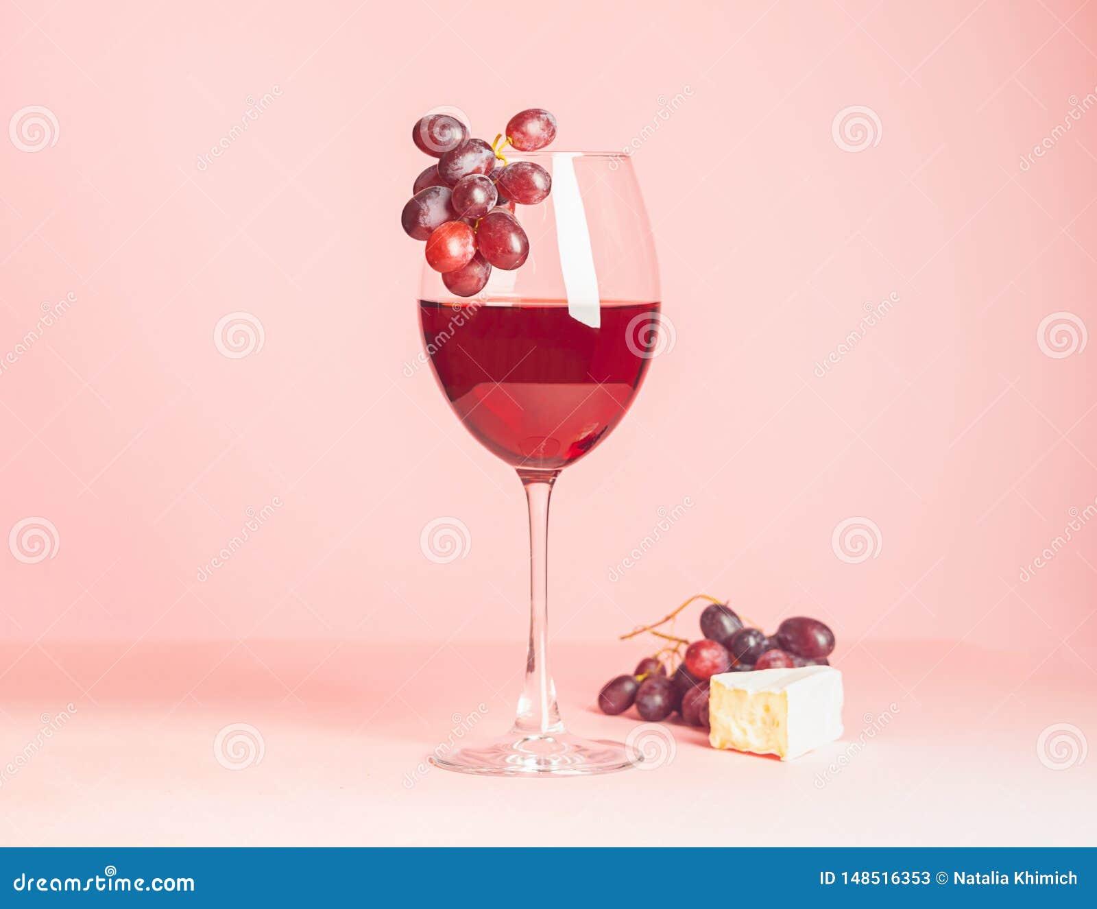Szk?o z czerwonym winem i przek?sk? na delikatnym r??owym tle Selekcyjna ostro?? kosmos kopii minimalista