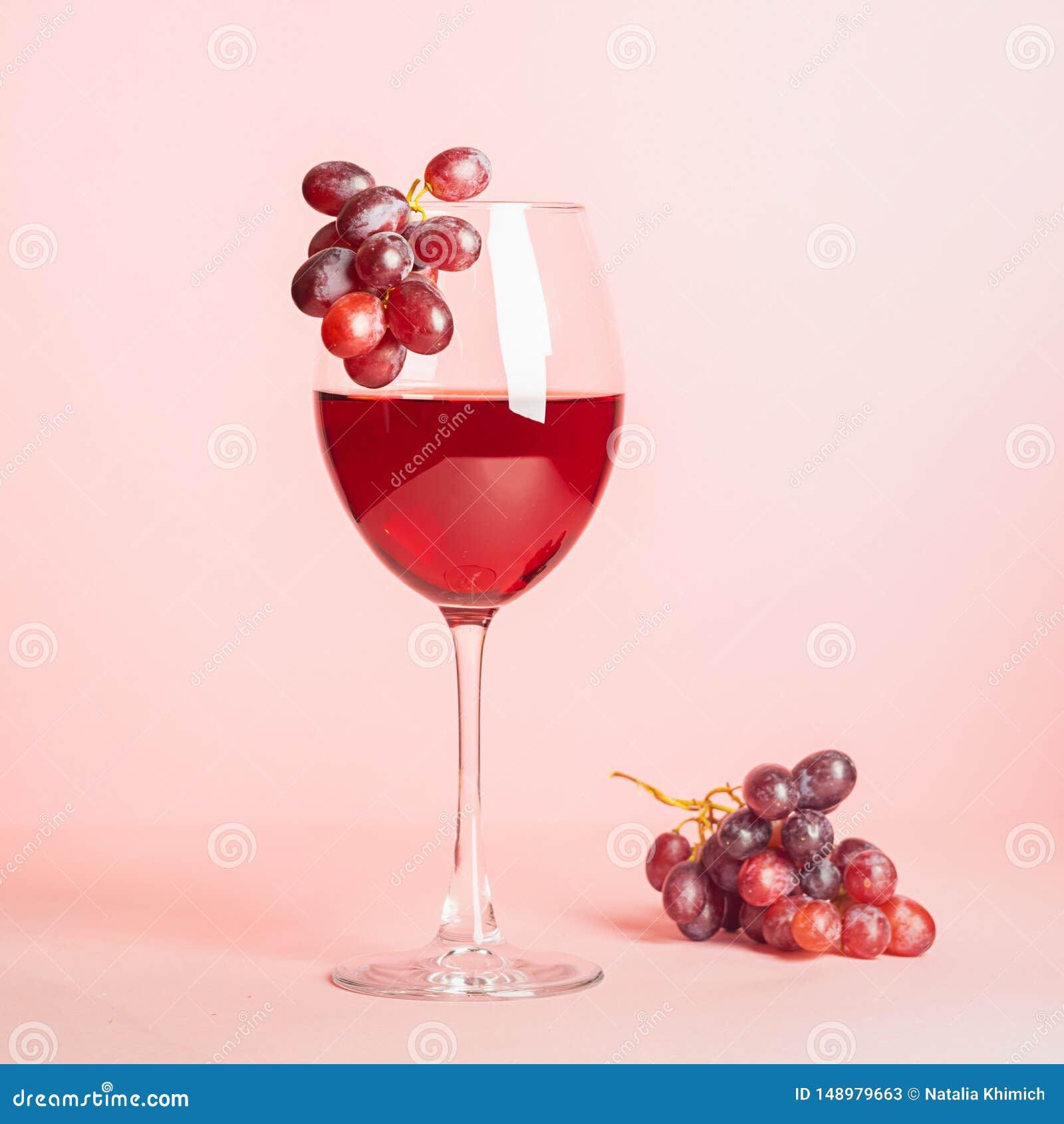 Szk?o z czerwonym winem i wi?zka winogrona na delikatnym r??owym tle Selekcyjna ostro?? kosmos kopii minimalista