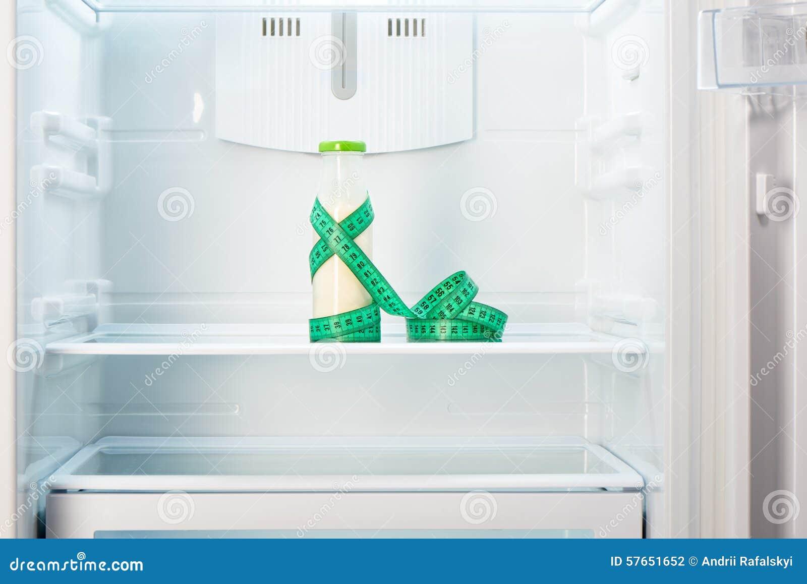 Szklana butelka jogurt z pomiarową taśmą na półce otwarta pusta chłodziarka