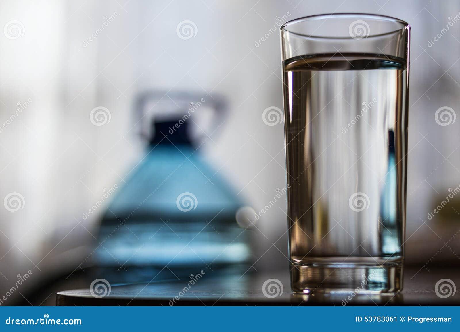 Szklana filiżanka z wodą i plastikową butelką