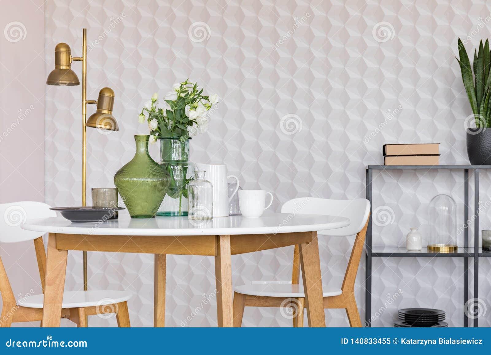 Szklana waza z kwiatami na białym drewnianym stole z talerzem, kawowymi kubkami i słojami, istna fotografia z kopii przestrzenią