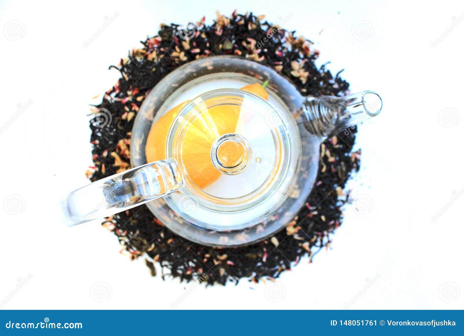 Szklany przejrzysty teapot na bia?ym stole i rozpraszaj?cy woko?o czarnej herbaty z additives