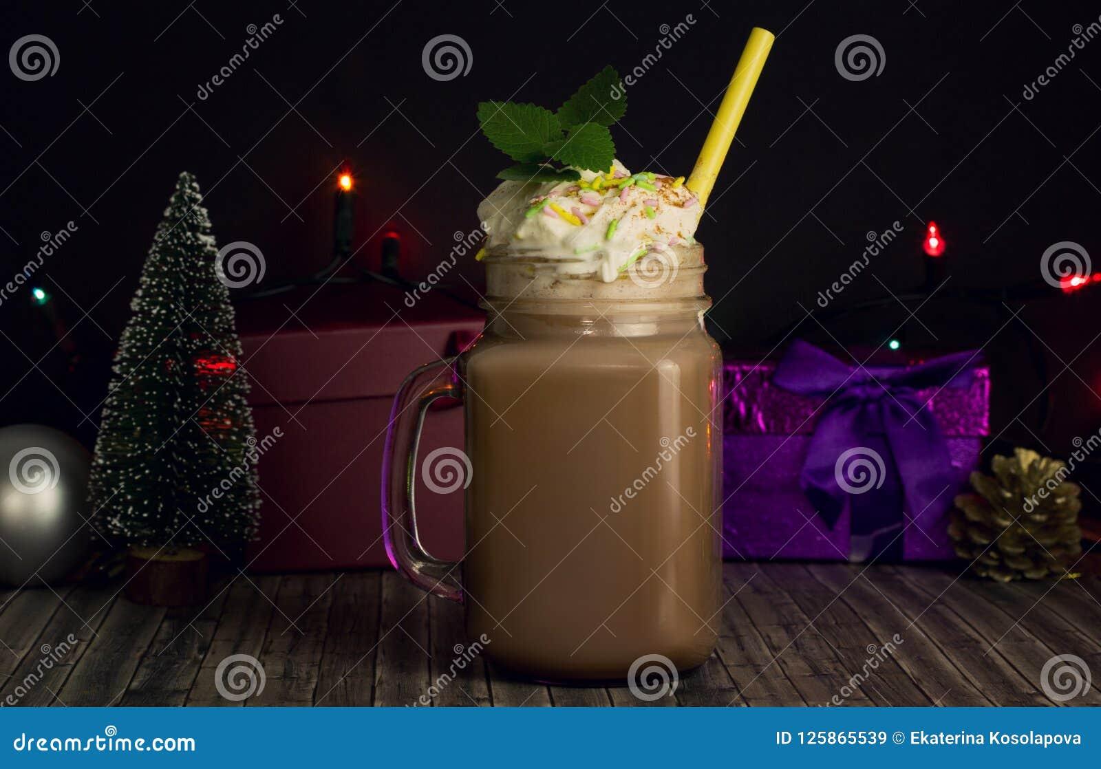 Szklany słój z kakao lub gorącą czekoladą z Bożenarodzeniowymi atrybutami