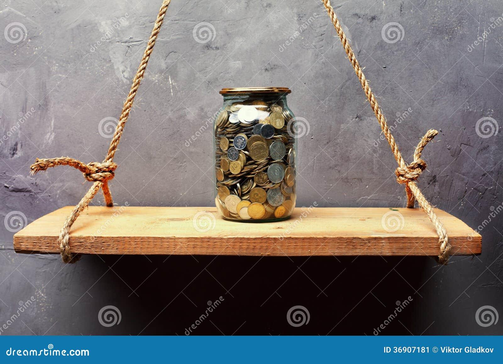 Szklany słój z monetami na starej drewnianej półce