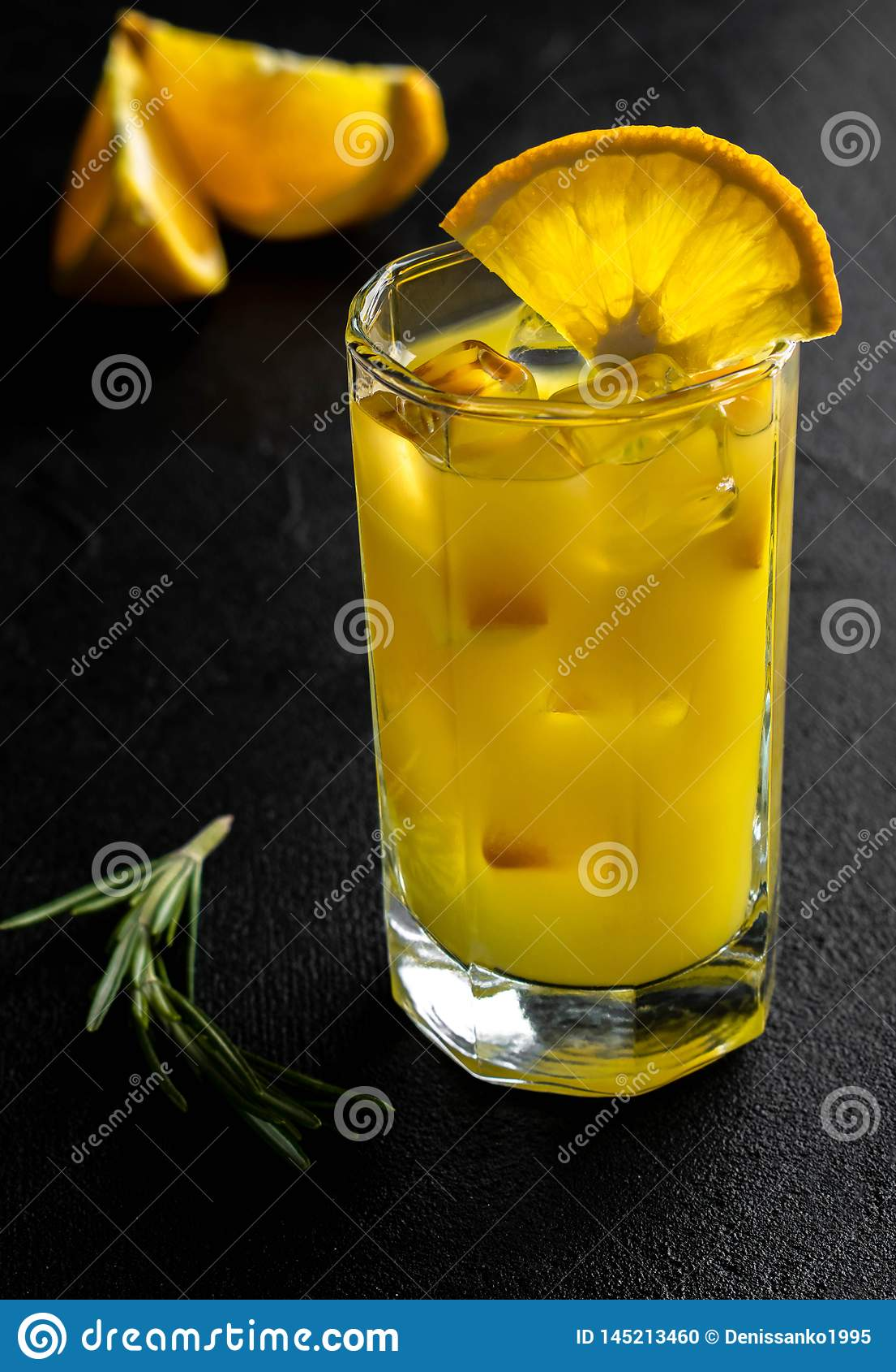 Szklany sok pomarańczowy z lodem i plasterki pomarańczowi z rozmarynami rozgałęziamy się na czarnym tle