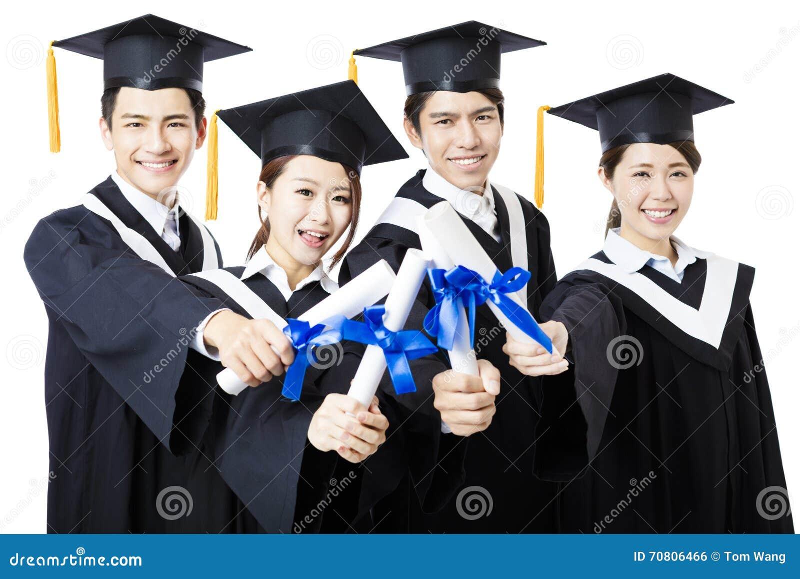 Szkoła wyższa absolwenci stoi i ono uśmiecha się w skalowanie togach