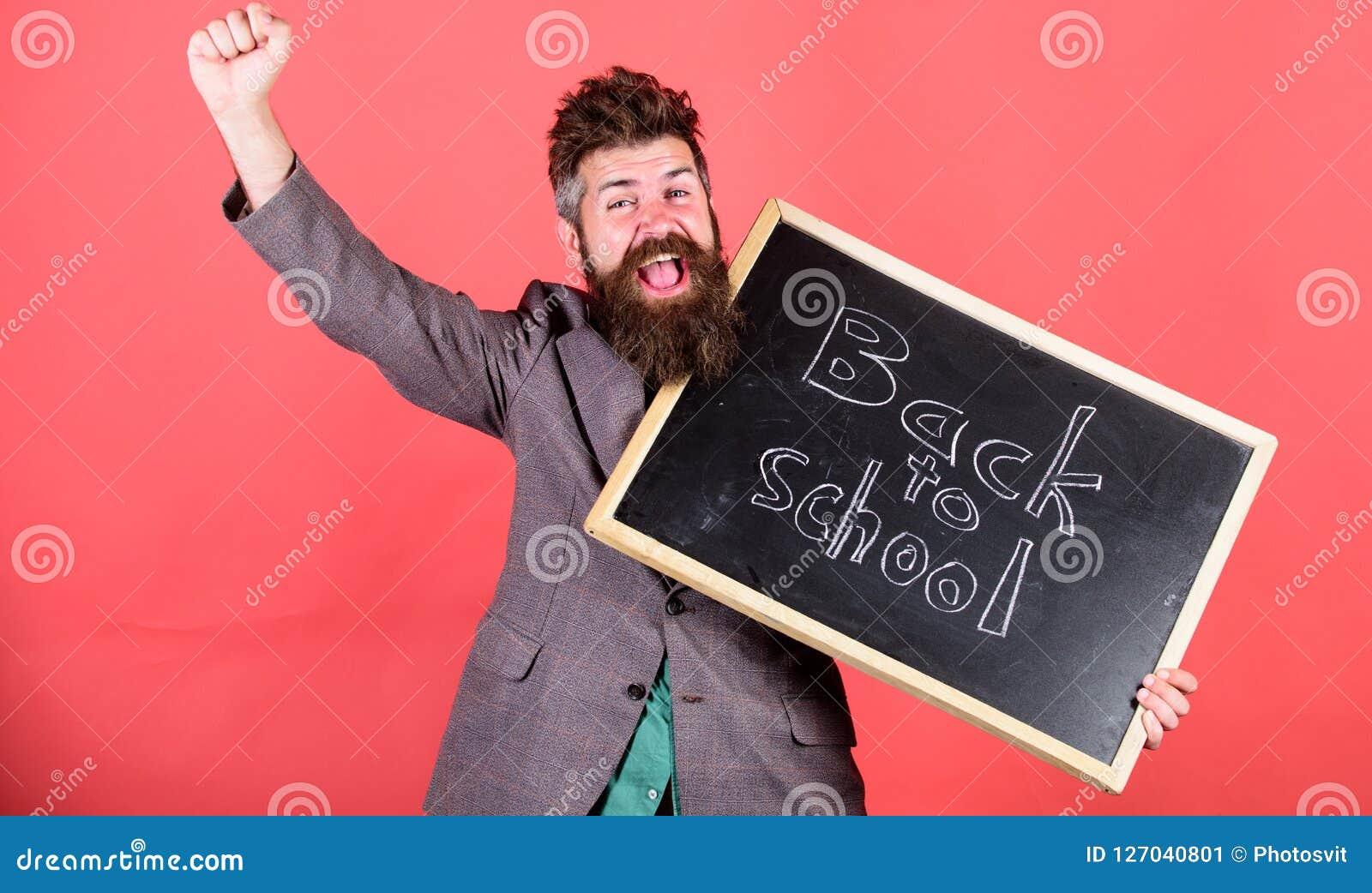 Szkoły i studiowania pojęcie Nauczyciel wita uczni szkoła podczas gdy chwyta chalkboard inskrypcja z powrotem pozytyw