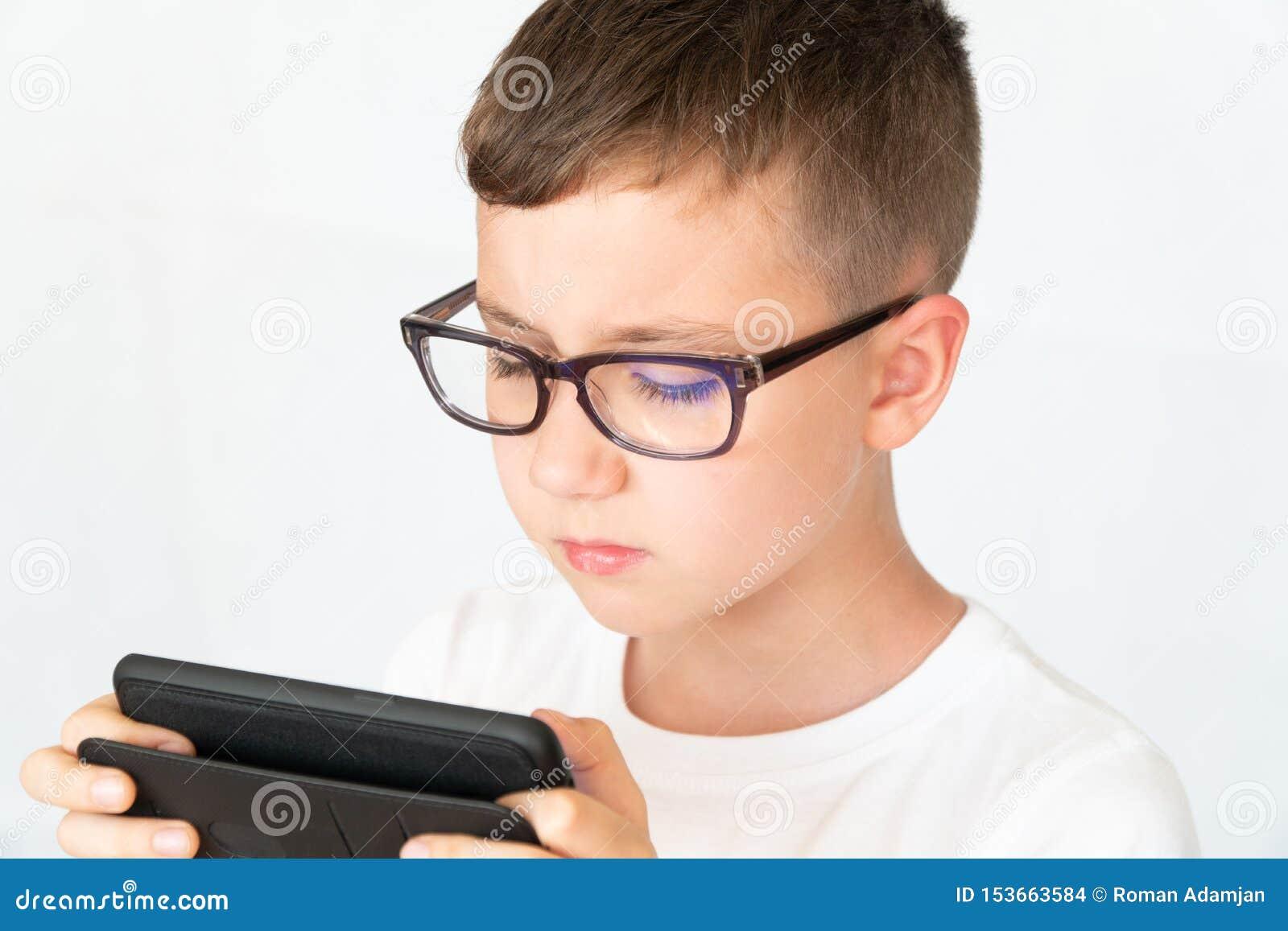 Szkolna chłopiec patrzeje przystojnego smartphone wideo w szkłach,