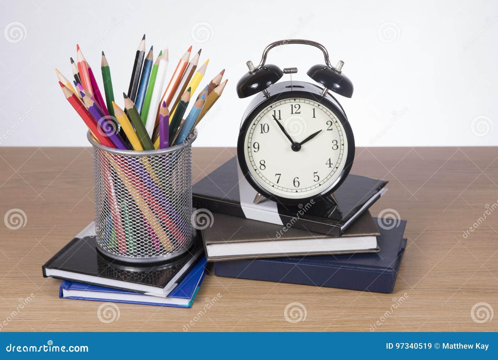 Szkolne książki, ołówkowe kredki i budzik,