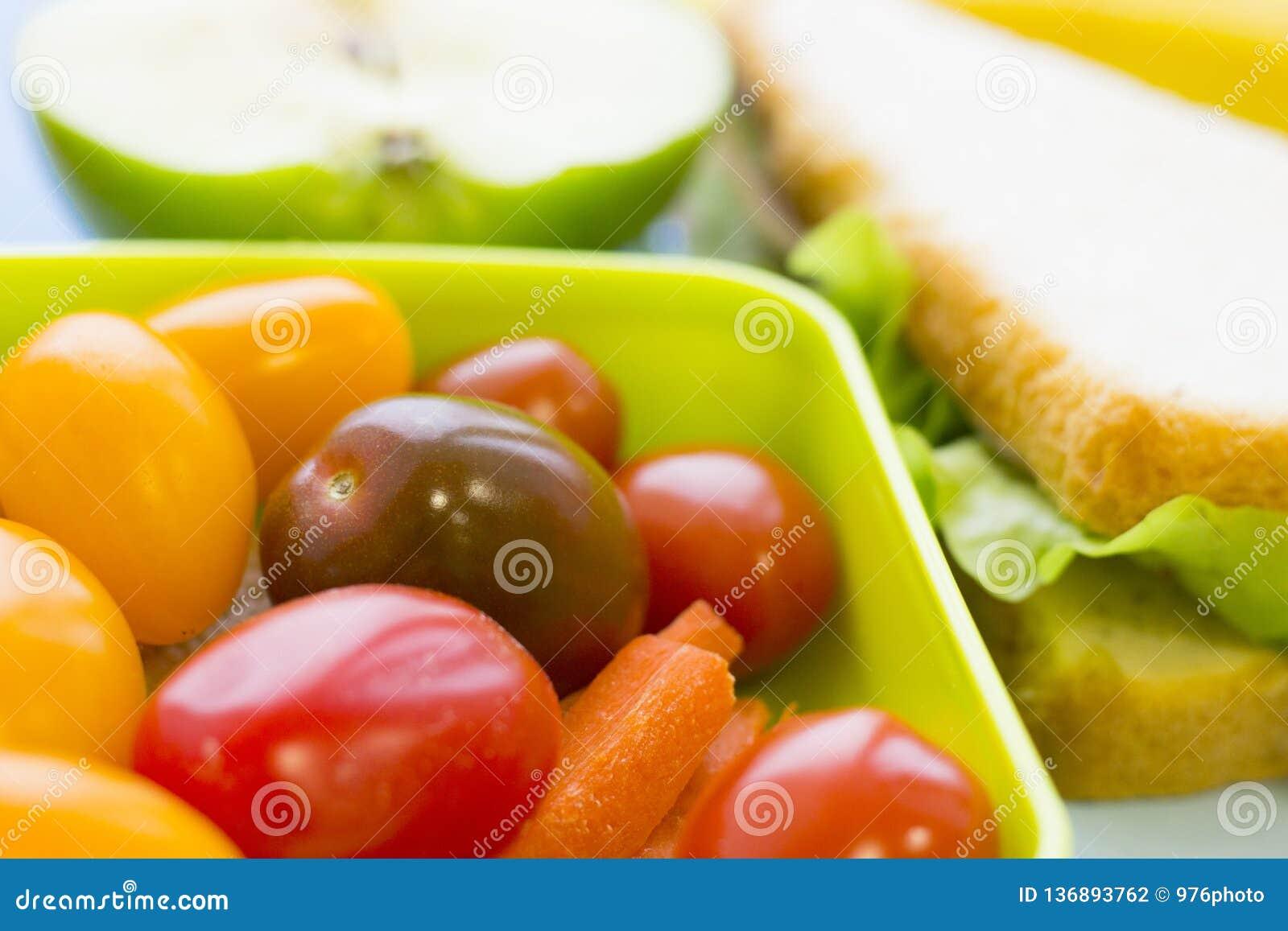 Szkolnego lunchu pudełko Chleb, jabłko, cukierki, dziecko kukurudze, marchewka i pomidory w zielonym plastikowym zbiorniku,