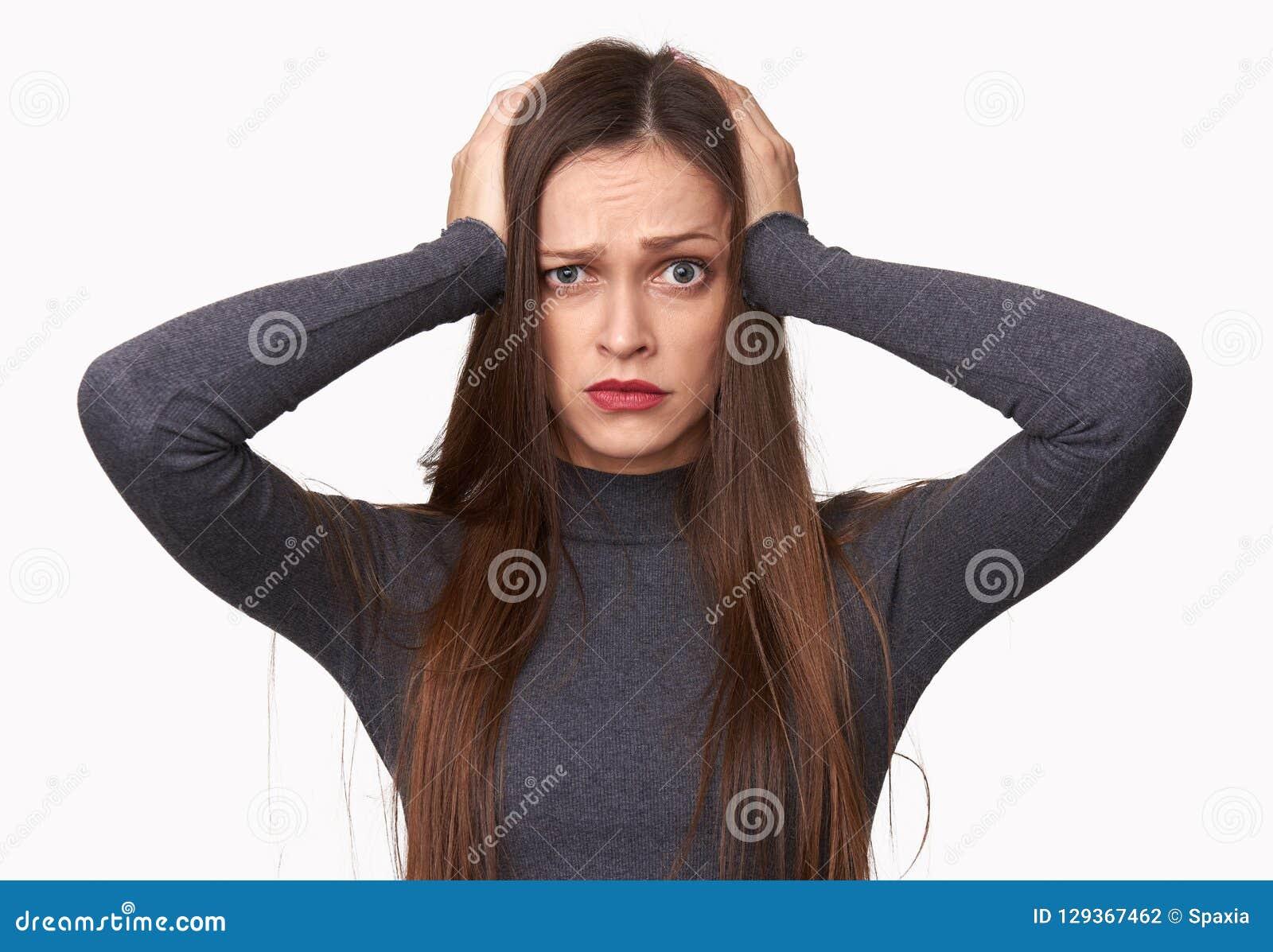 Szokująca kobieta trzyma jej ręki na głowie